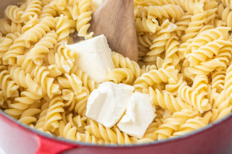 Up close image of cooked noodles in a red pot with cream cheese and a wooden spoon.