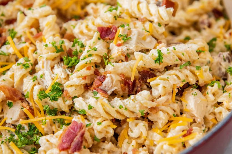 Up close image of creamy ranch pasta tossed with chicken, cheese, bacon and parsley on top.