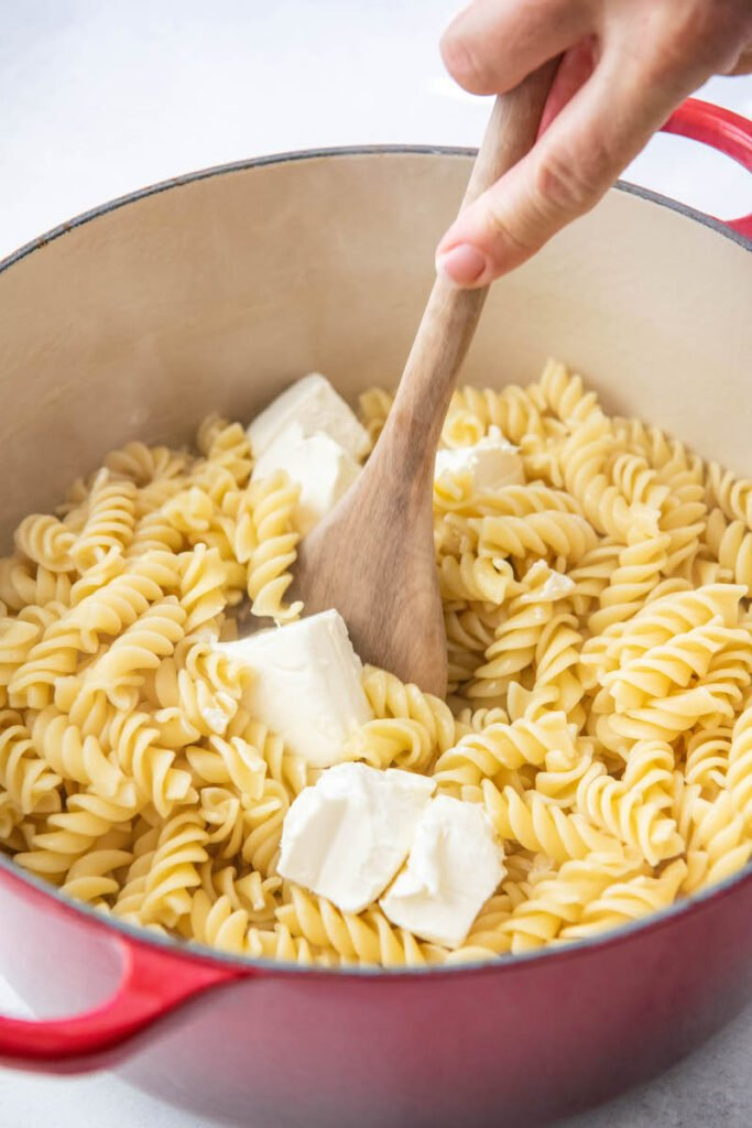 Cream Cheese is stirred into cooked rotini noodles.