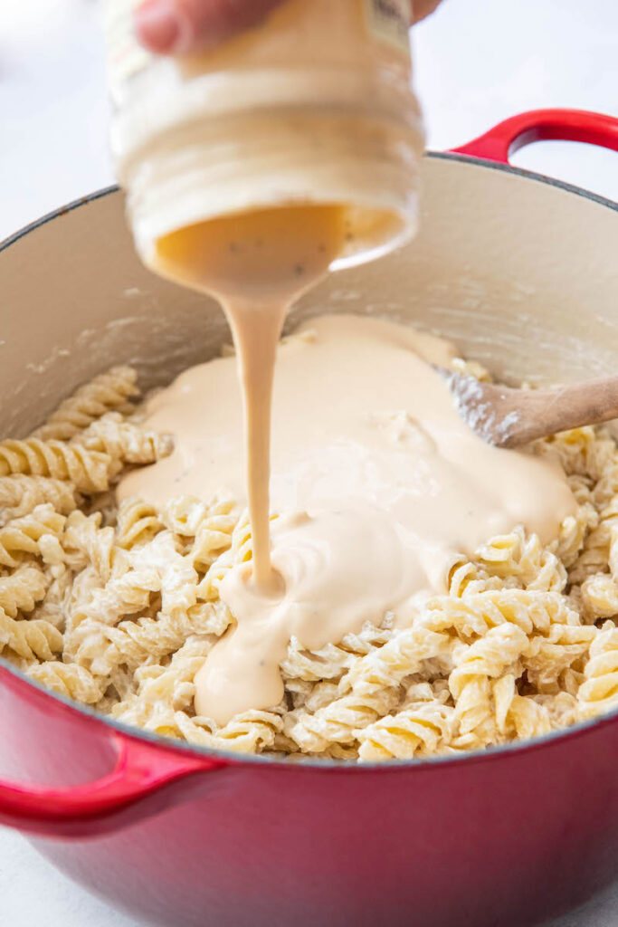 Alfredo sauce is poured on top of noodles in a large stock pot.
