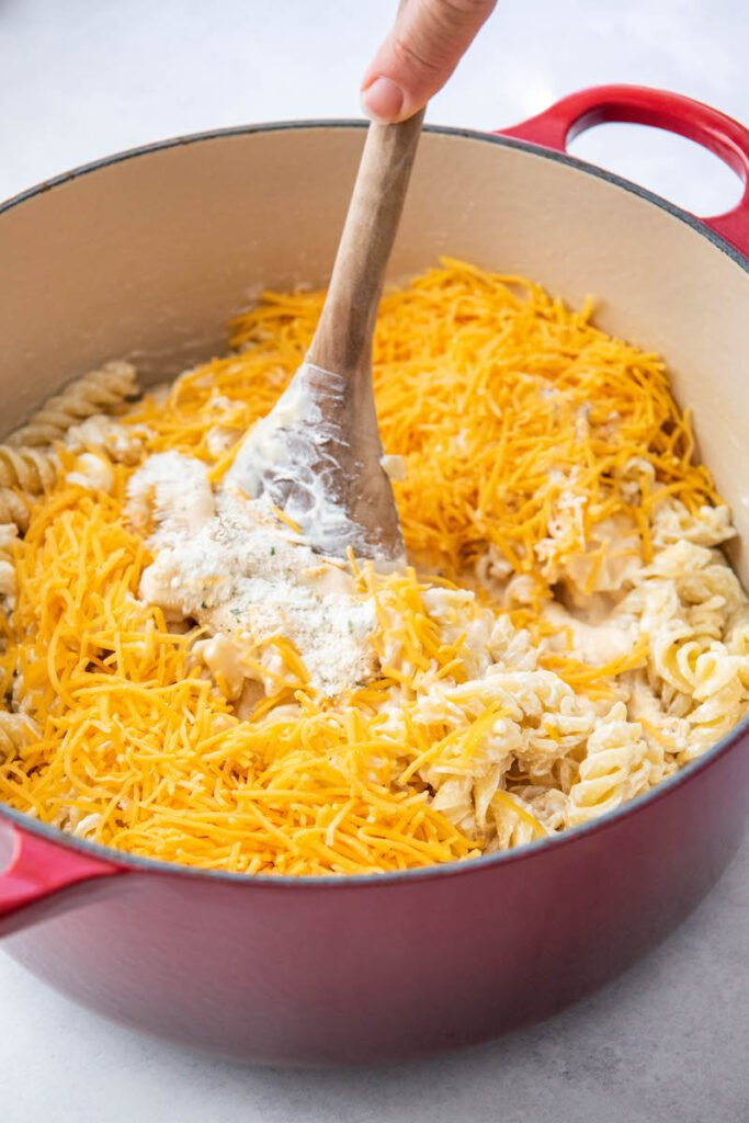 Shredded cheddar cheese is mixed on top of the creamy pasta.