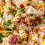 Up close image of chicken bacon ranch pasta in a pot with a wooden spoon.