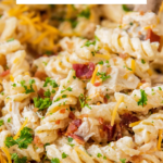 Up close view of chicken bacon ranch pasta in a pot with cheese on top.