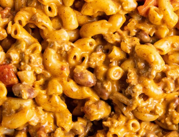 Elbow noodles are coated in yellow cheese mixed with brown ground beef.