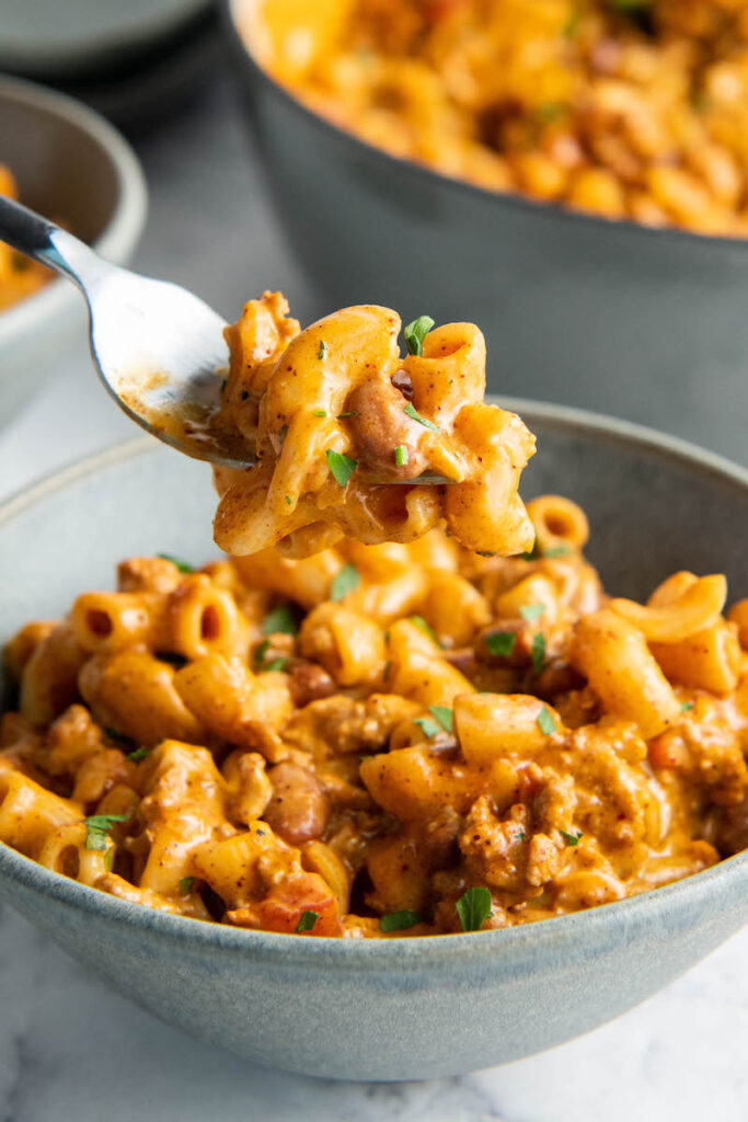 A fork is holding up a bite sized portion of chili Mac above a bowl.