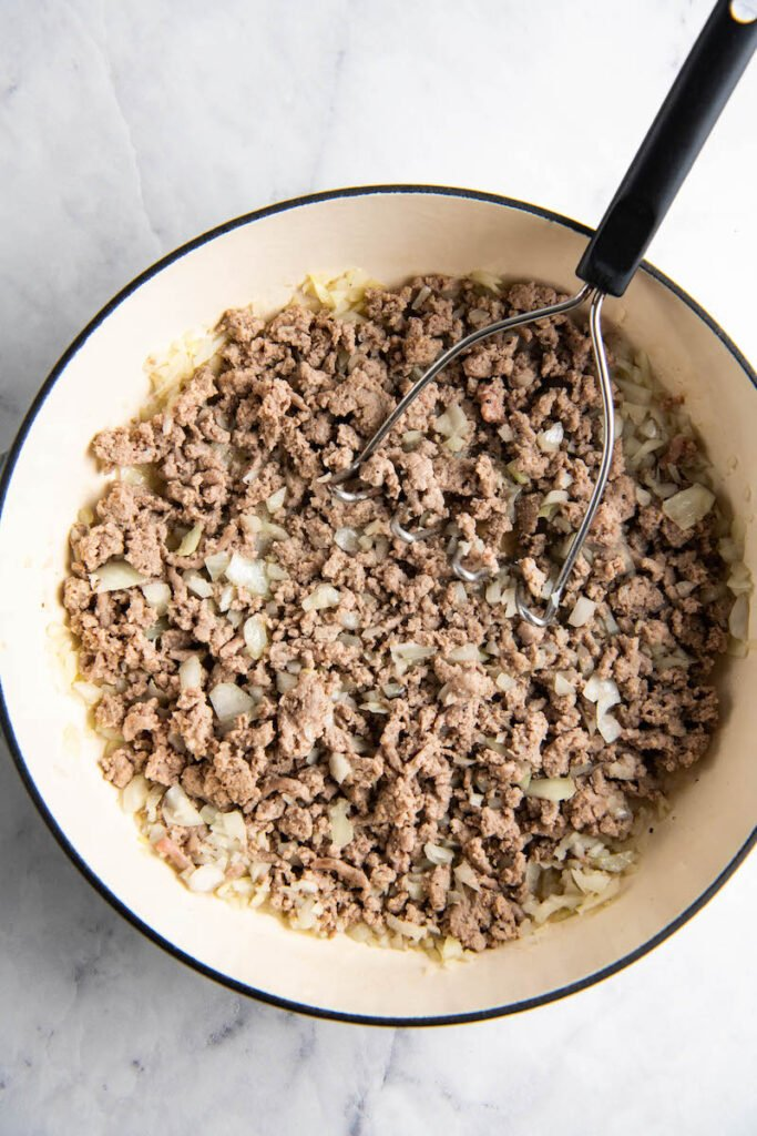 Ground meat is being mixed in a large white dutch oven.