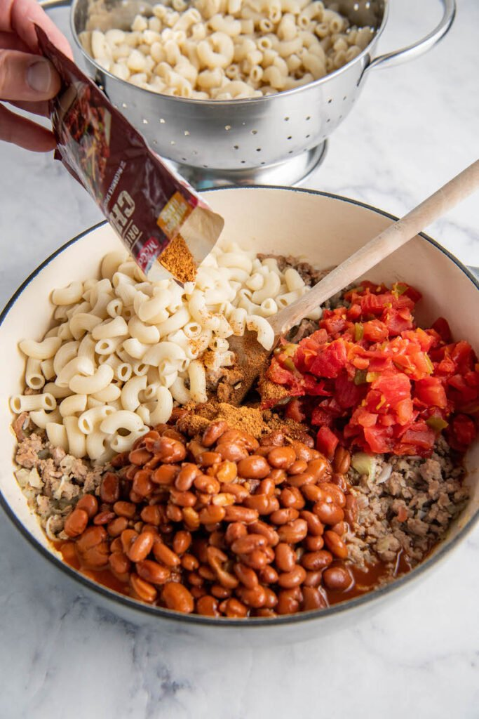 Beans, noodles, Rotel, ground meat and seasoning are mixed together in a large pot.