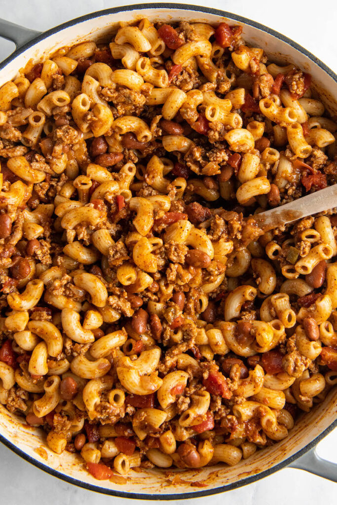 A large spoon is placed in a pot full of chili mac.