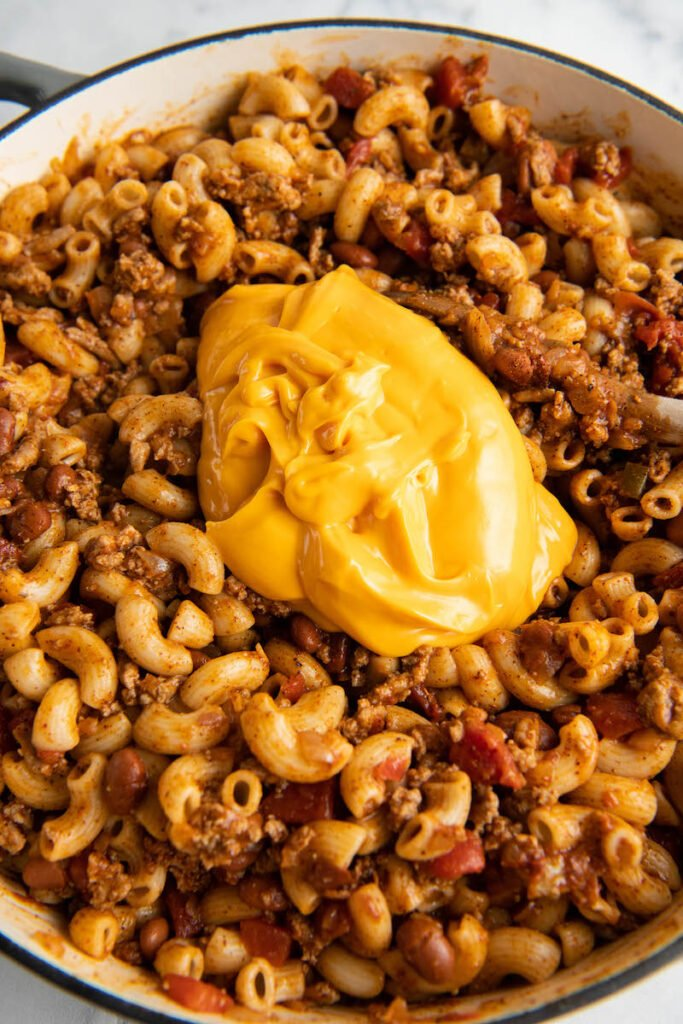 Yellow Velveeta cheese is placed on top of the mixture.