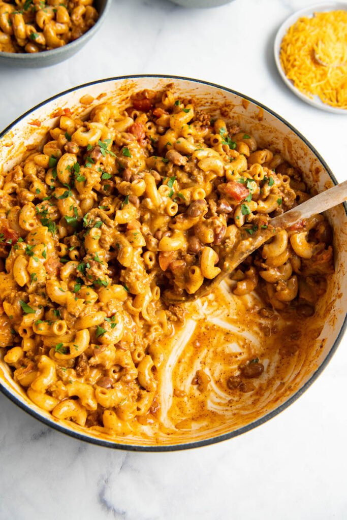 A skillet has a portion of chili mac missing.
