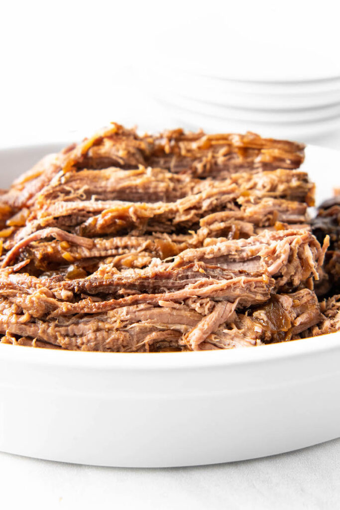 A close up shot shows shredded beef stacked in a clean white bowl.