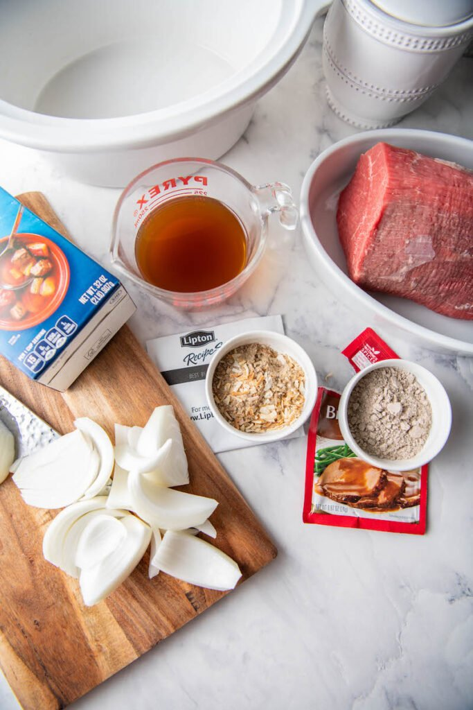 The ingredients for crockpot shredded beef are spread out on a white countertop.