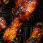 Up close image of a chicken drumstick in an air fryer basket.