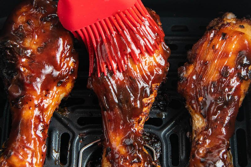 Chicken drumsticks being brushed with bbq sauce in an air fryer basket.