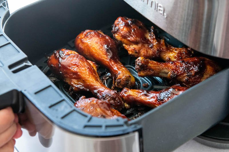 Chicken legs in an air fryer basket being pulled out of air fryer.