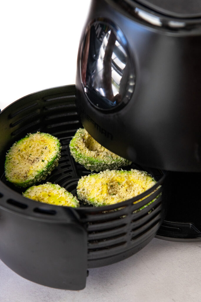 Four halves of avocados coated in breadcrumbs being inserted into an air fryer.
