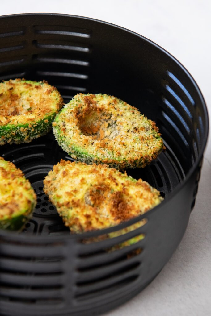 Air Fried Avocados are sitting in a basket of an air fryer.