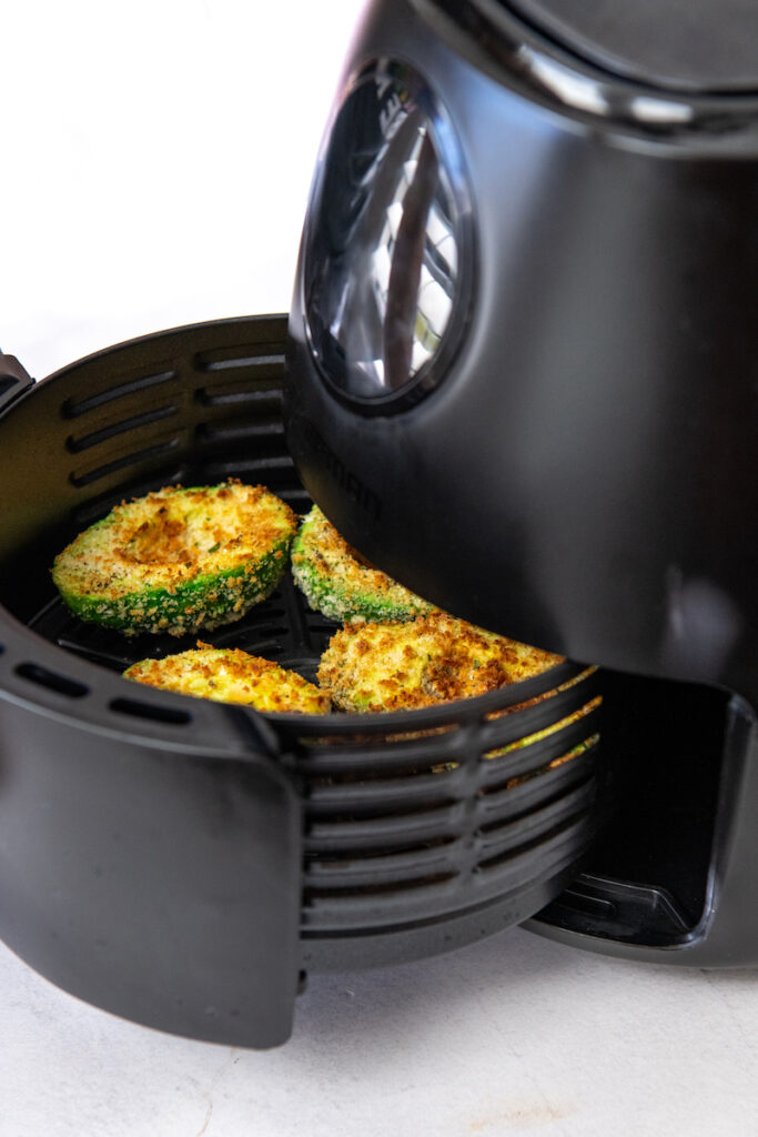 Four halves of fried avocados coated in breadcrumbs being removed from an air fryer.