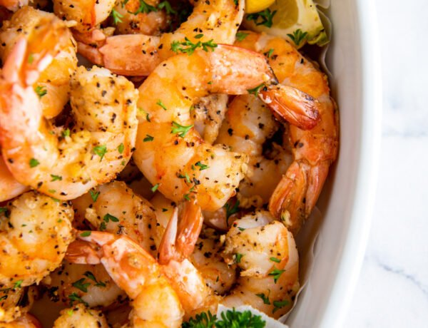 Air fried shrimp are placed in a white serving dish with a slice of lemon.