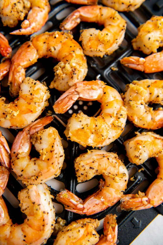 Cooked shrimp are in the air fryer basket.