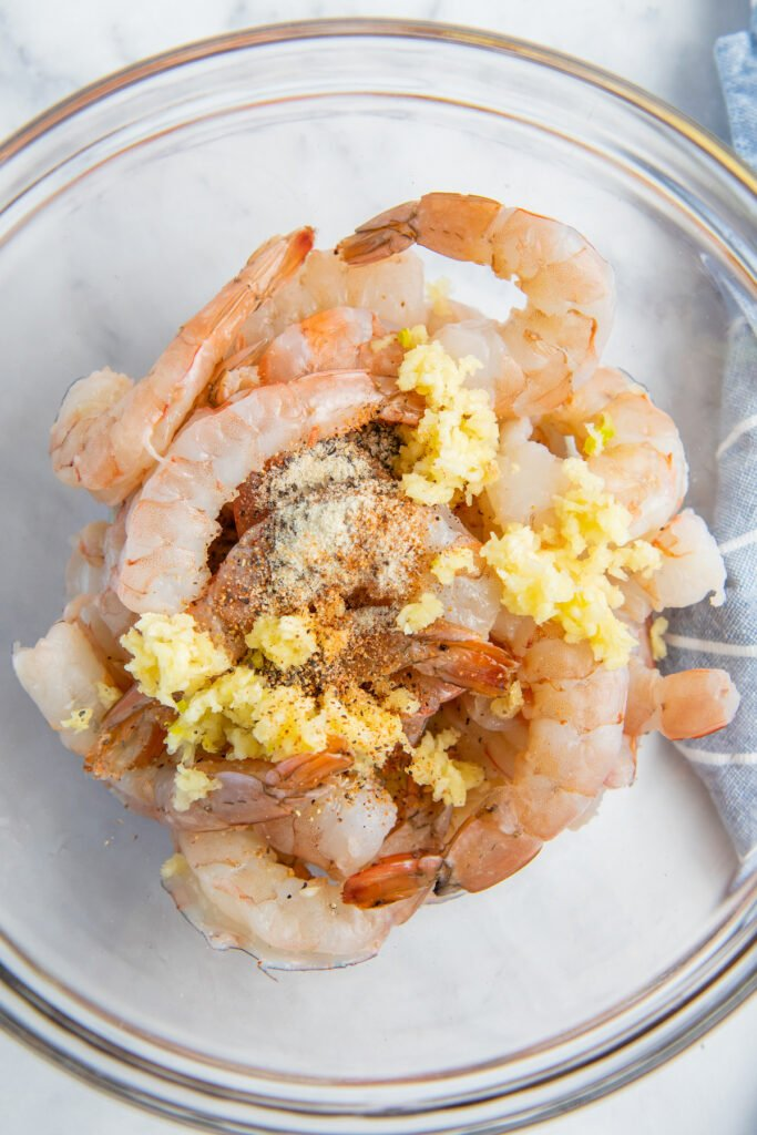 Shrimp are in a glass bowl and covered with seasonings and minced garlic.
