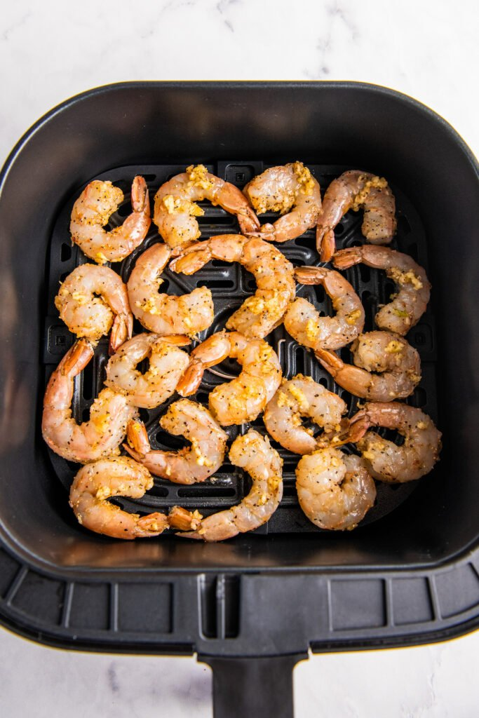 Shrimp are placed in the bottom of the air fryer basket.