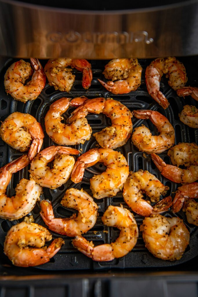 Cooked shrimp are in the air fryer.