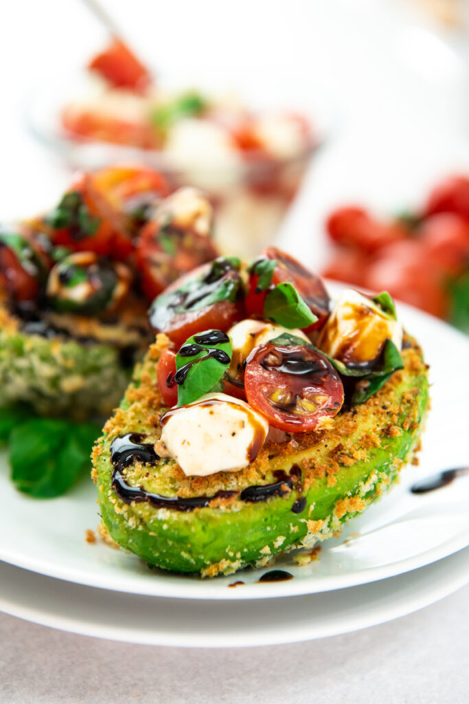 Two stuffed avocados are on a white plate, ready to be eaten.