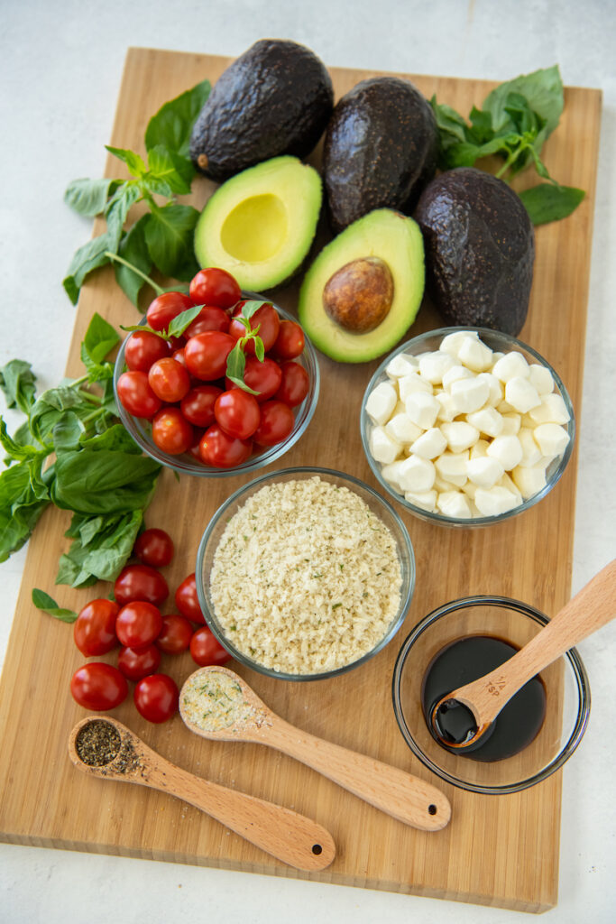 The ingredients for capers stuffed avocados are placed on a wooden cutting board.