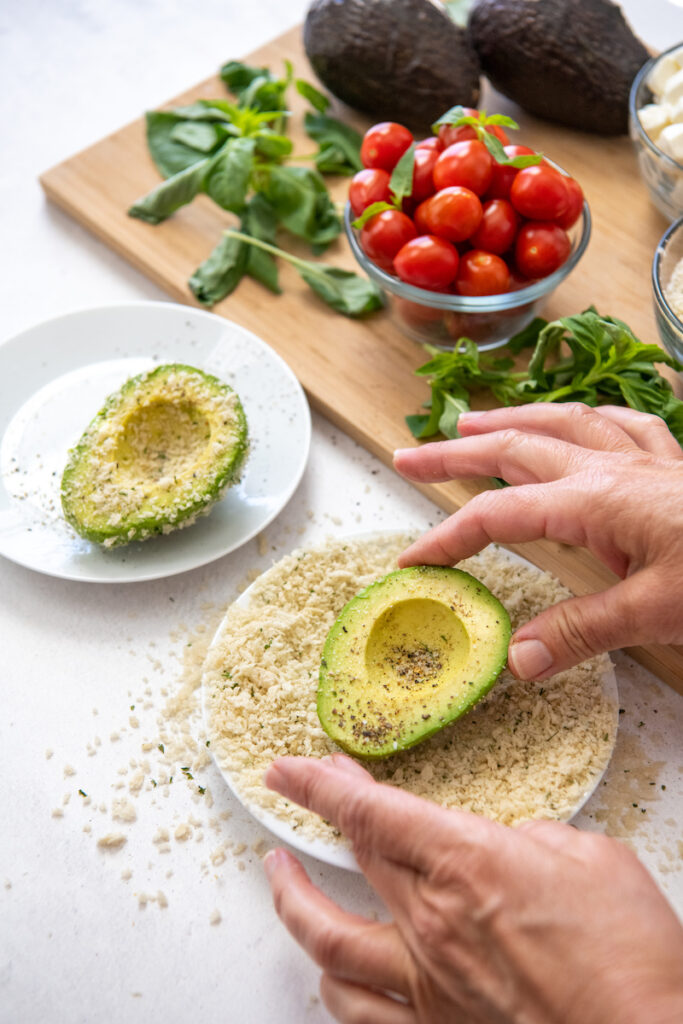 Avocado halves are rolled in breadcrumbs on a white plate.