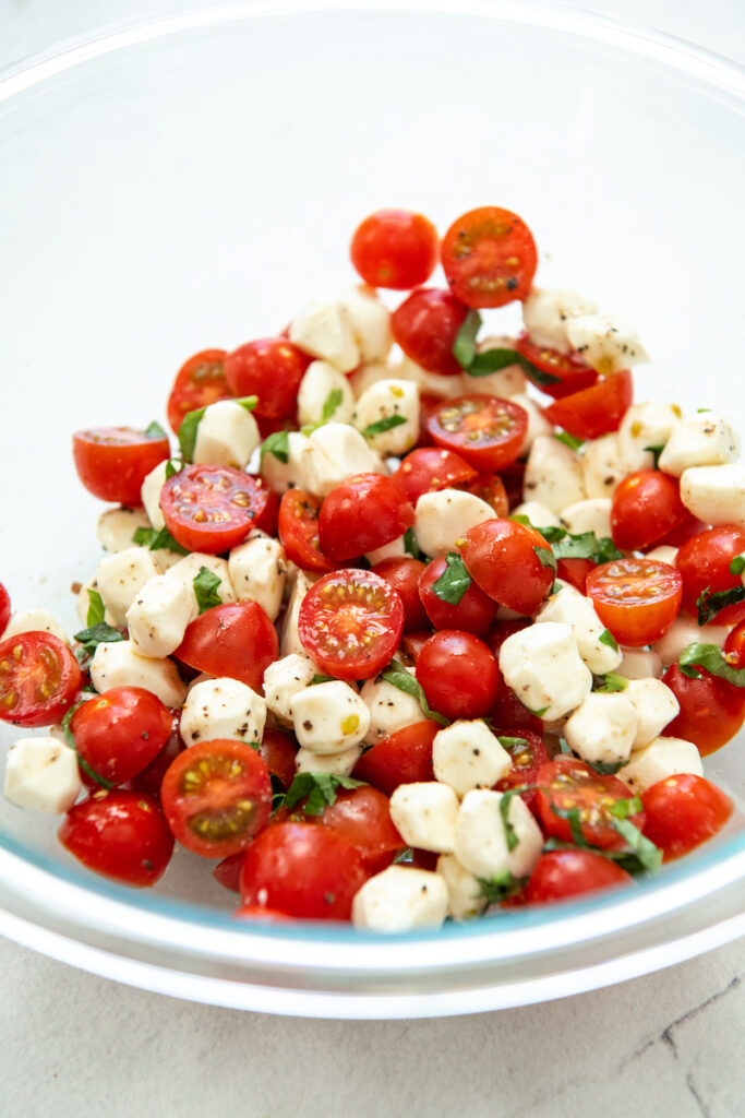 The fresh caprese ingredients are mixed together in a glass bowl.