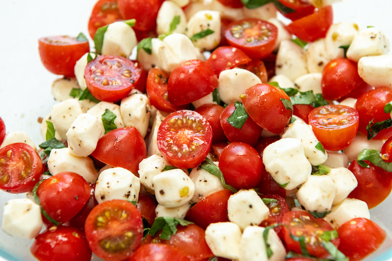 Caprese Salad tossed together in a glass bowl.