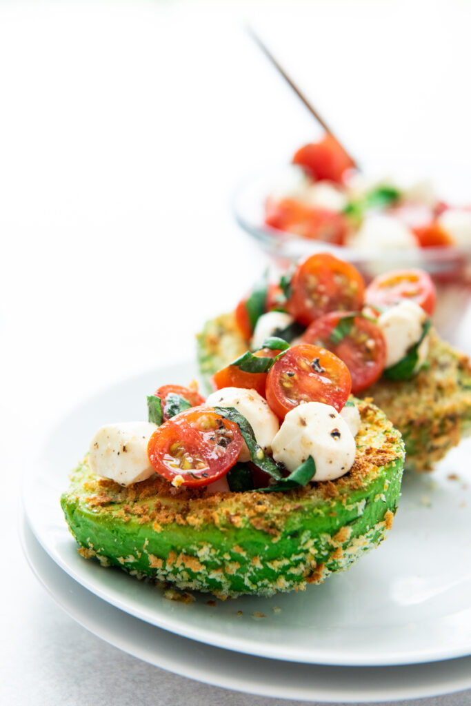 Avocados are stuffed with caprese filling on white plates.