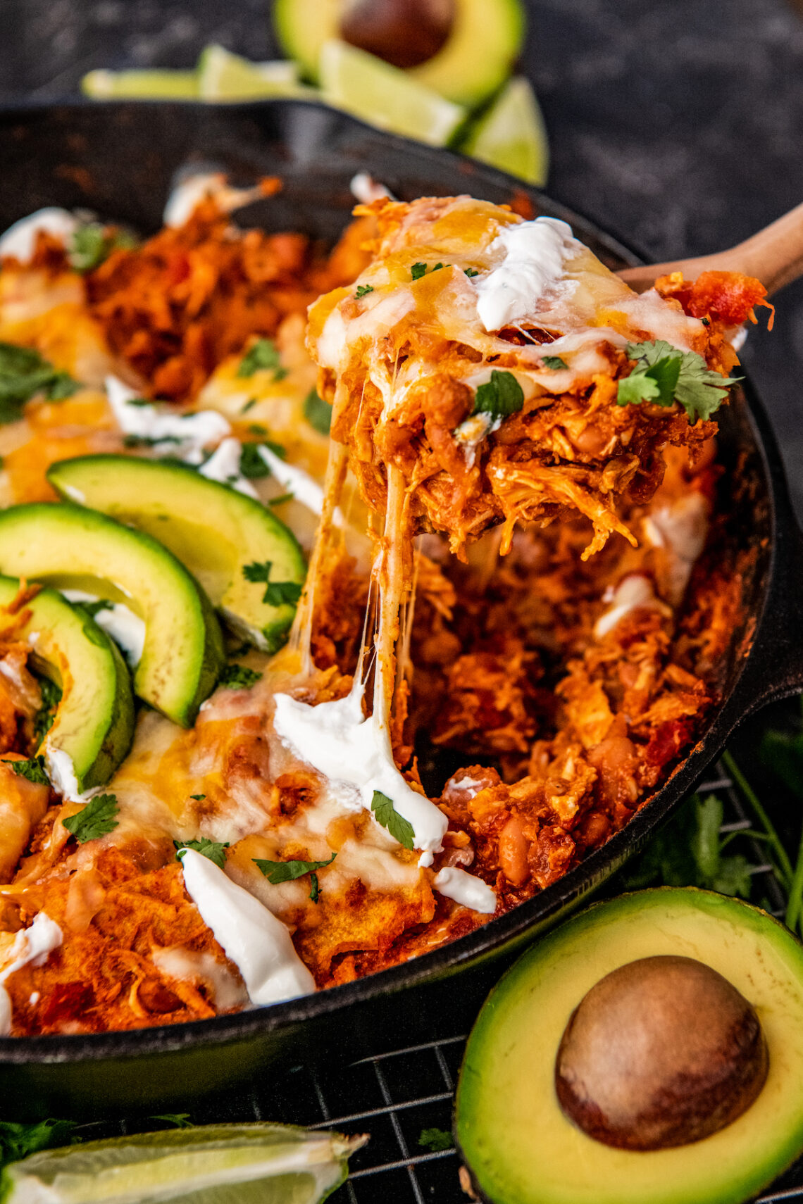 A large spoon is scooping out a portion of chicken enchiladas from a black skillet.