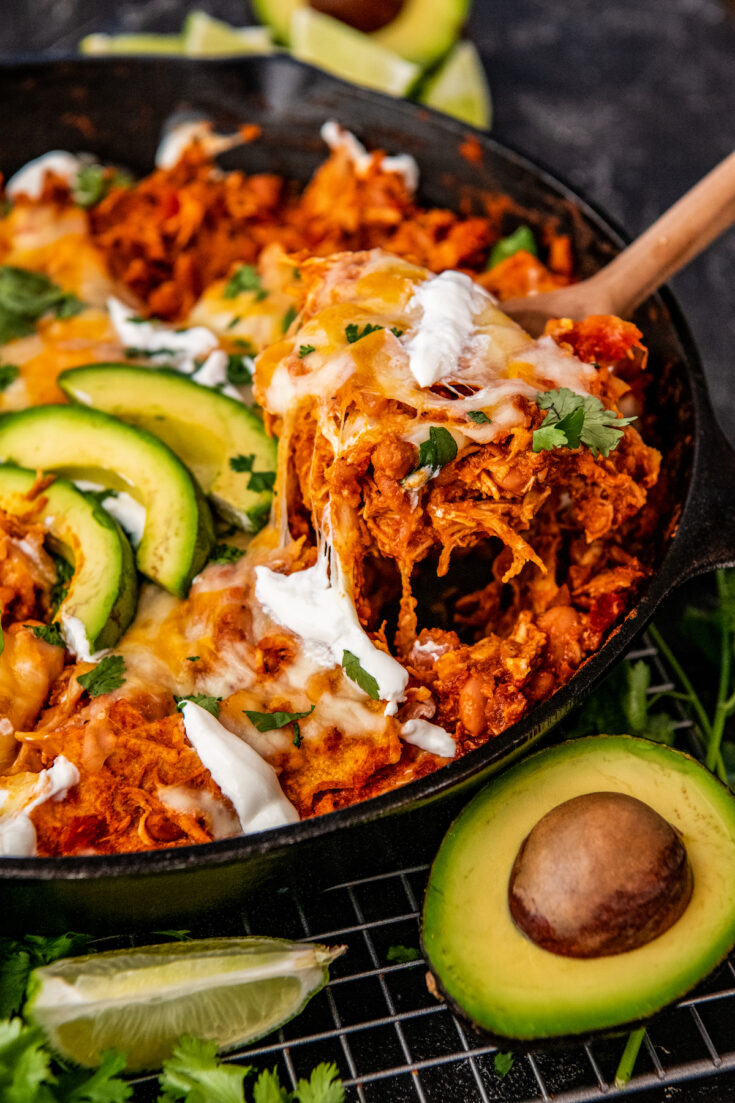 A serving of enchiladas is being taken out of the skillet with a large spoon.