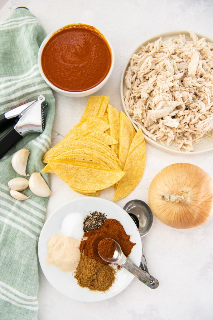 The ingredients for chicken enchiladas are placed on a white surface.