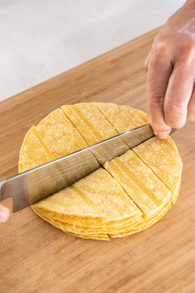 Corn tortillas are being sliced with a large knife.