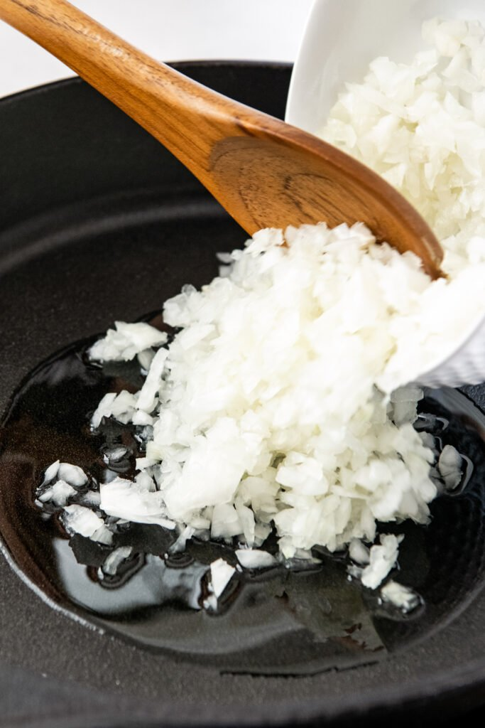 Diced onions are being poured into a black skillet.