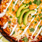 Avocado halves and bunches of cilantro are placed around a skillet full of enchiladas.