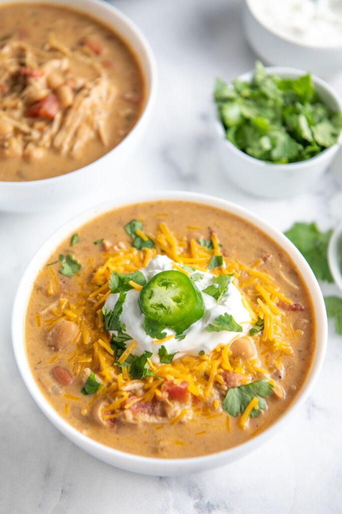 A white bowl with chicken chili topped with sour cream and jalapeno slice.