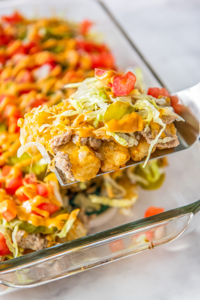 A serving of cheeseburger casserole is being lifted from a large dish.