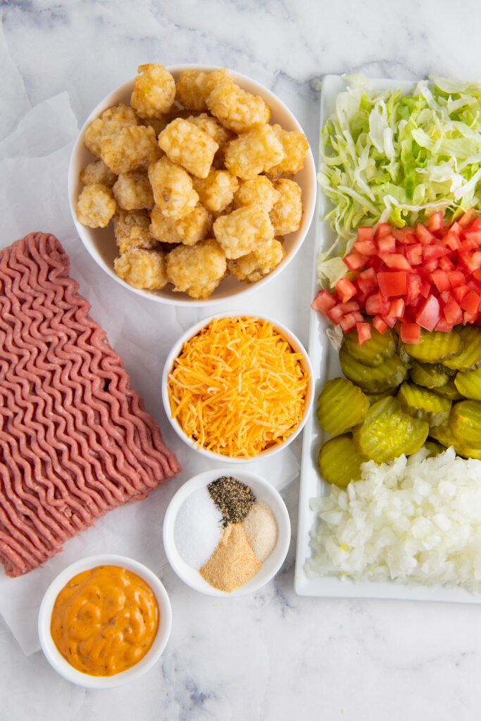 The ingredients for cheeseburger casserole are displayed on a white surface.
