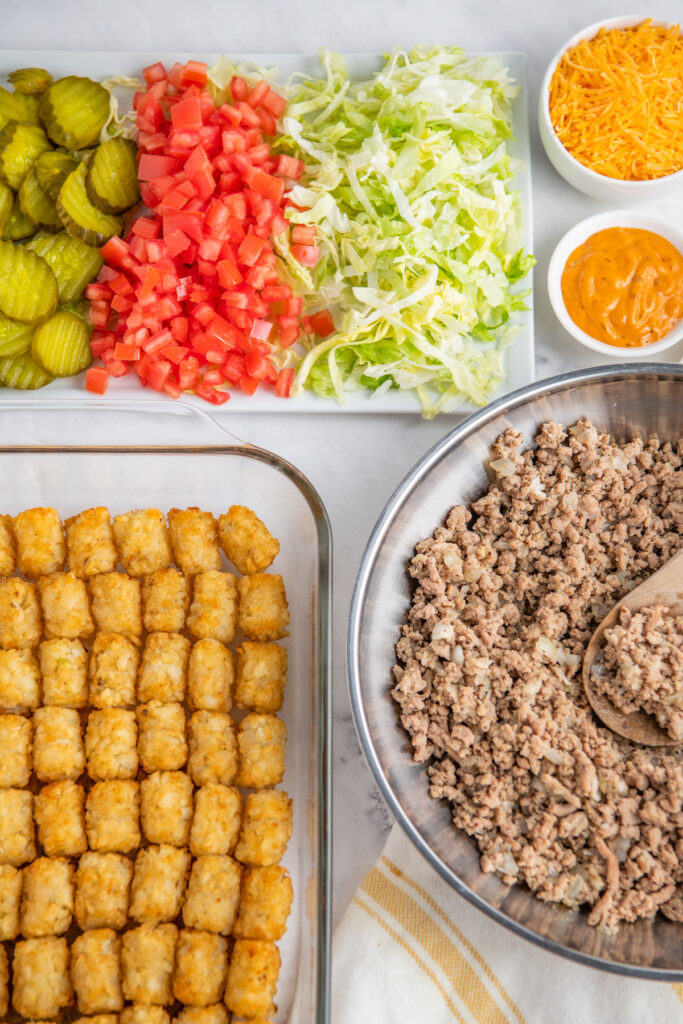 Baked tater tots are placed next to a skillet full of cooked ground meat and a plate of fresh veggies.