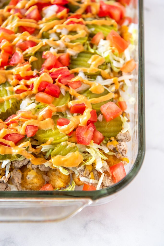The toppings for cheeseburger casserole have been placed on top of the melted cheese.