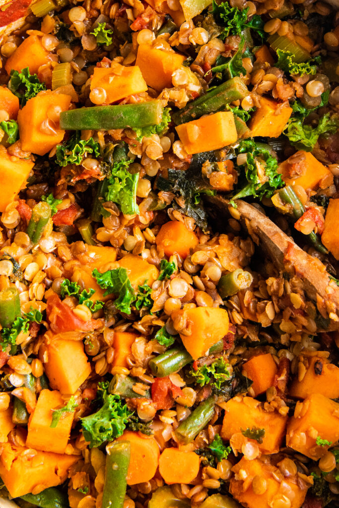 A close up image shows the ingredients for lentil stew are fully cooked.
