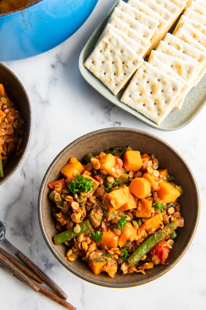 Saltine crackers are placed next to a bowl of lentil stew.