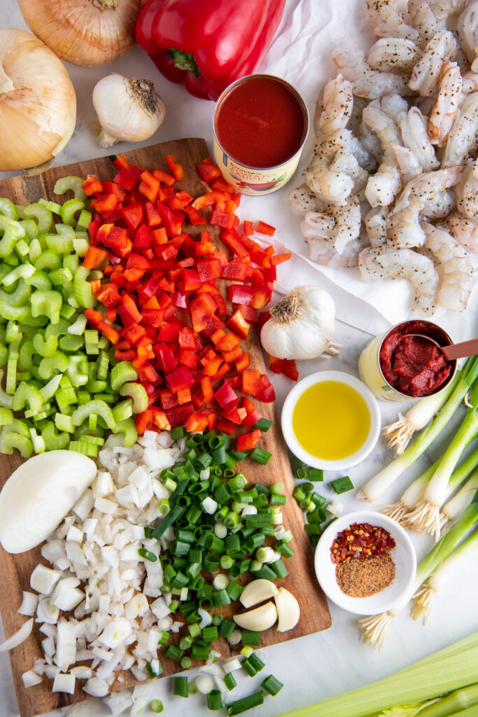 Chopped onion, celery, bell pepper, green onion, tomato sauce, tomato paste and shrimp on a cutting board