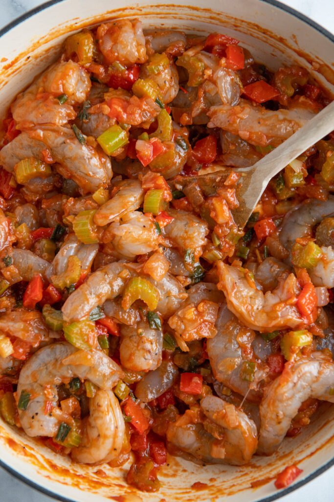 Raw shrimp in a skillet with red sauce and bell peppers.
