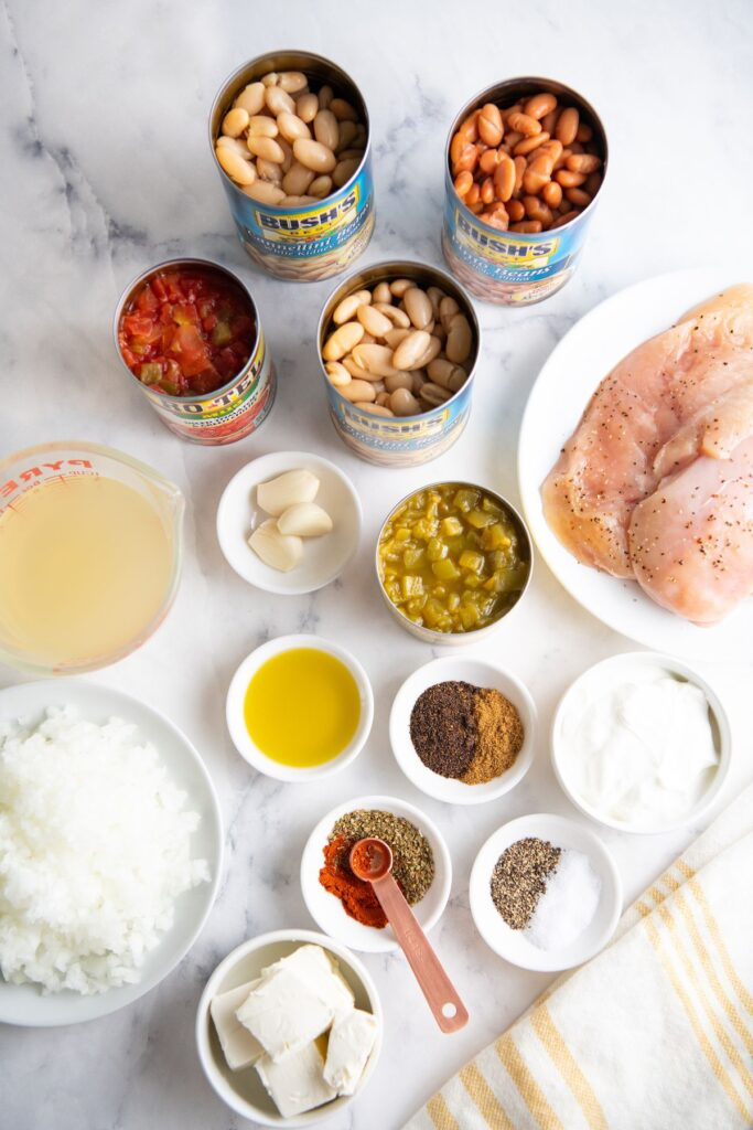 Picture of 3 cans of beans, can of tomatoes, seasonings, chicken broth, chicken breast, chopped onion, cream cheese and sour cream.