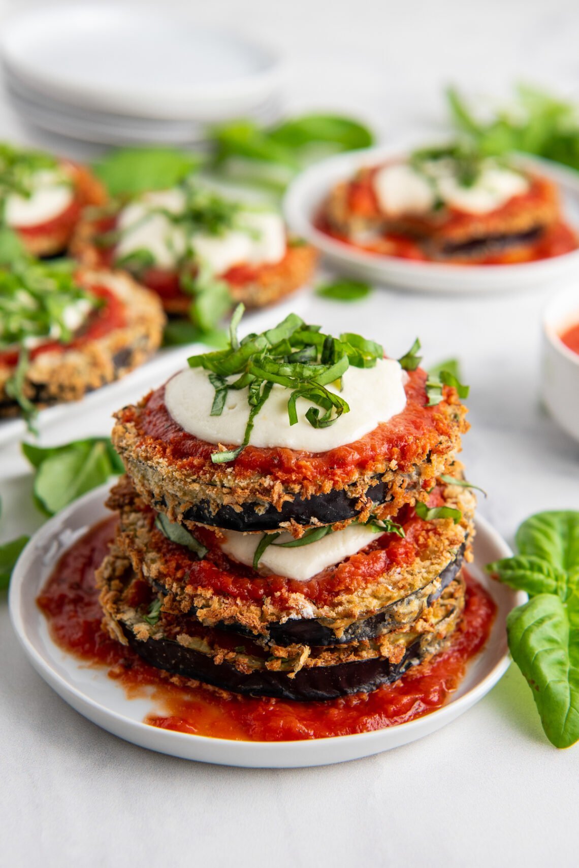 Eggplant Parmesan topped with mozzarella, sauce and basil stacked on a plate